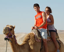 Couple ride camel in Israel.