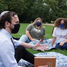 Students in masks sitting on a lawn and talking