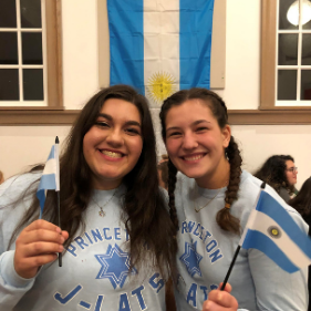 Two girls pose in front of the Argentinian flag