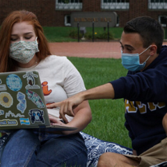 Two students wearing masks look at a laptop