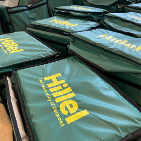 An array of green lunchboxes with a yellow Hillel logo on top
