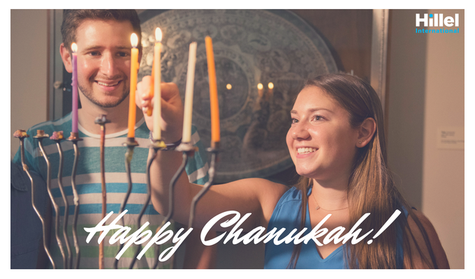 "Text reads ""Happy Chanukah"" with an image of two students lighting the Menorah."