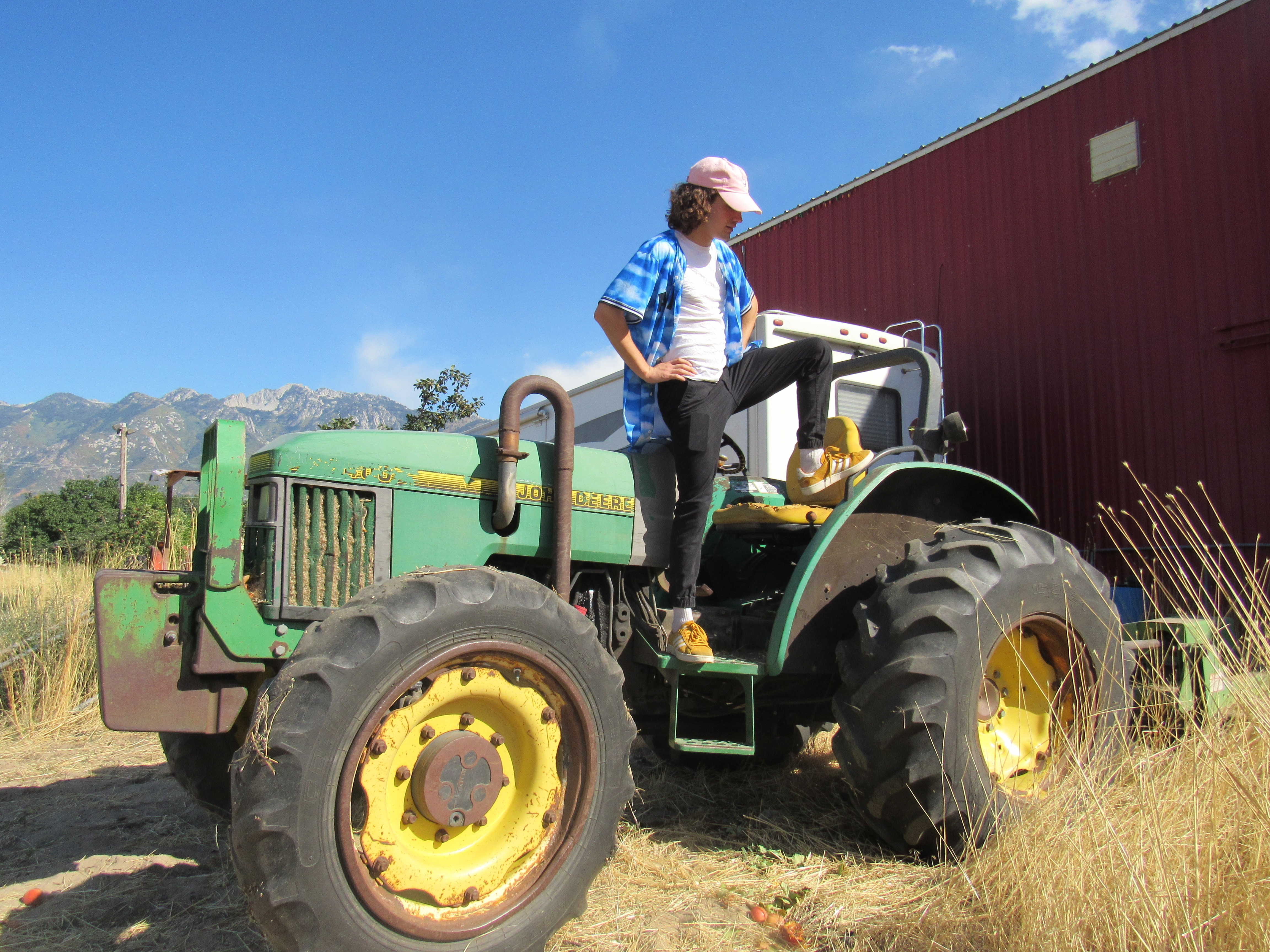 A boy with a blue shirt, yellow shoes and a pink hat stands on the side of a tractor with one leg up on top of the wheel.