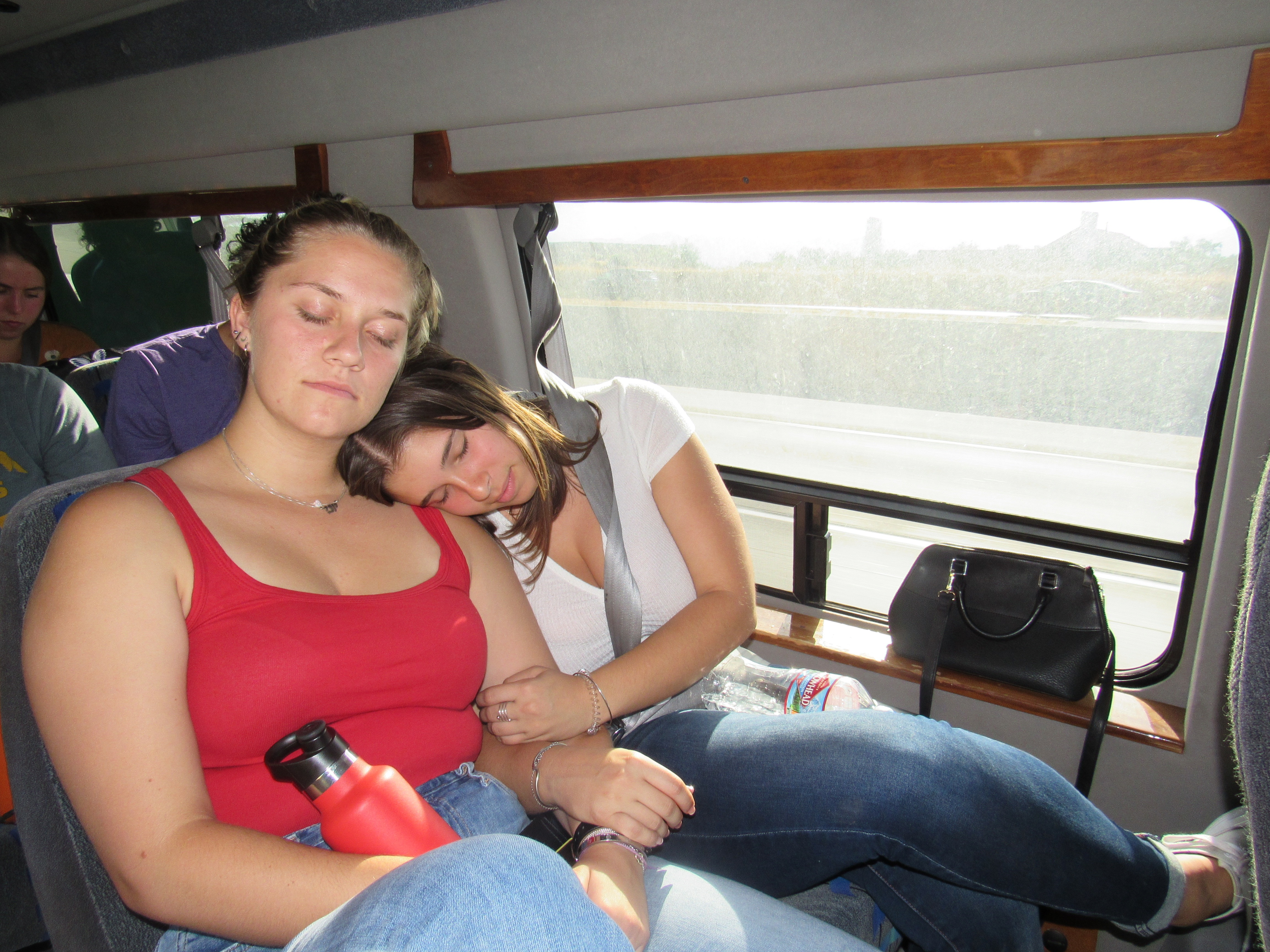Two girls lean against each other as they sleep on a van.